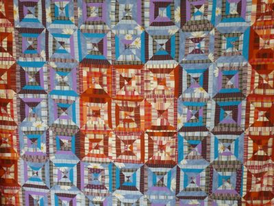Quilt in blau/orange mit Technik Log Cabin